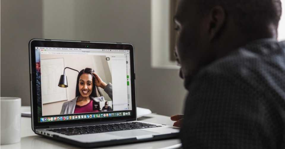 A shot of a video conference with a woman who can be seen smiling on screen. A man is sitting in front of the computer.
